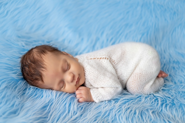 Neonato che dorme su una coperta blu