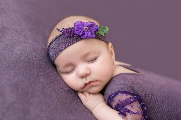 Neonato che dorme con le mani sotto la guancia.