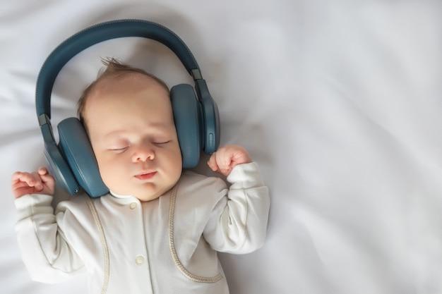 Neonato sorridente che ascolta la musica con le cuffie e sdraiato sul foglio bianco nel presepe, felice infanzia spensierata del bambino, immagine tonica, vista dall'alto, primo piano