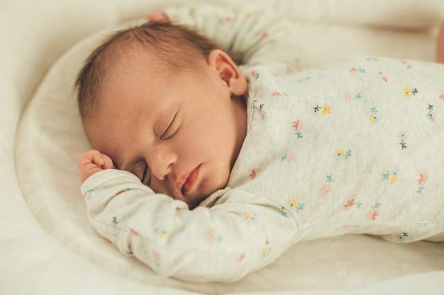 Neonato in vestiti caldi bianchi che dorme nel letto totalmente rilassato e si sente al sicuro