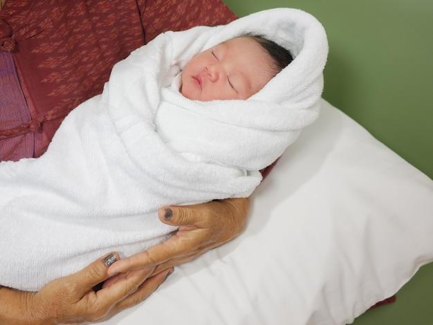 Neonato avvolto in un panno bianco dorme in un abbraccio