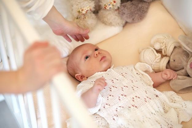 Il neonato carino giace nella culla e guarda la madre
