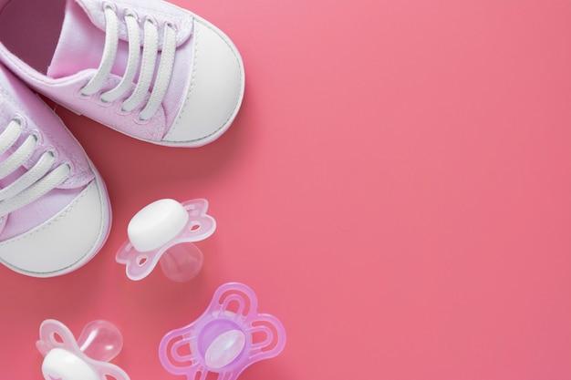 Scarpe neonato con succhiotti, tavolo rosa con spazio di copia.