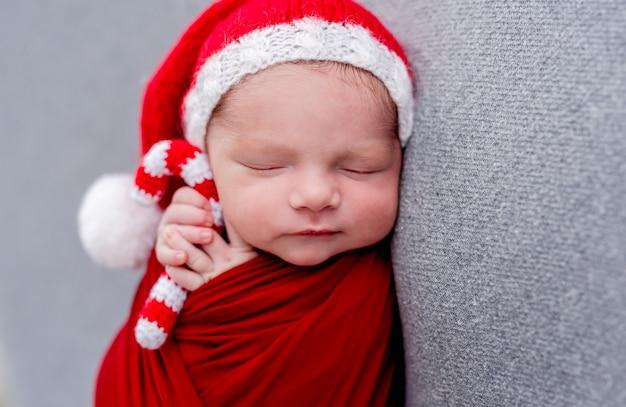 Neonato che dorme con caramelle natalizie a maglia