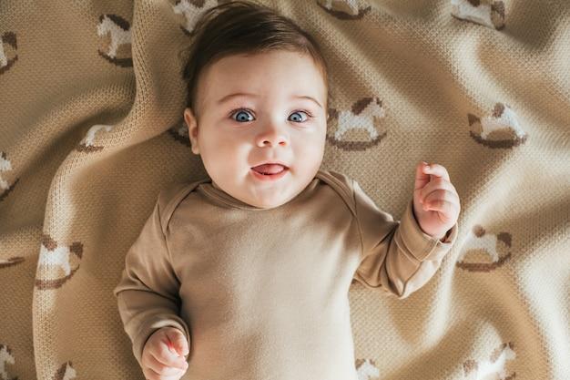 Ritratto del ragazzo del bambino appena nato in tuta beige che esamina la macchina fotografica sulla vista superiore del plaid