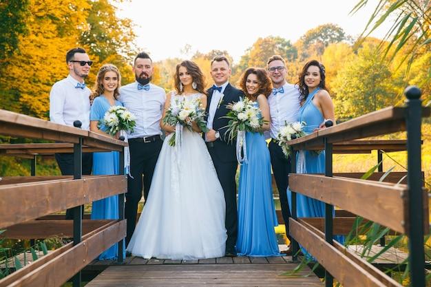 Coppia di sposini con testimoni dello sposo e damigelle in posa durante la cerimonia di nozze