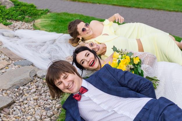 Sposi novelli con damigelle che si divertono alla cerimonia di nozze