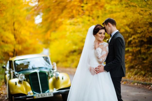 Coppie recentemente sposate che stanno l'automobile d'annata rossa seguente del yo in parco. sposa che tiene bellissimo bouquet e lo sposo che abbraccia la moglie