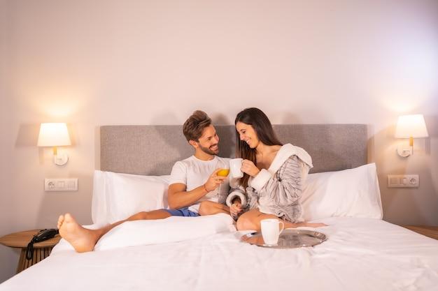 Una coppia appena svegliata in pigiama che mangia caffè e succo d'arancia per colazione nel letto dell'hotel la mattina, lo stile di vita di una coppia innamorata.