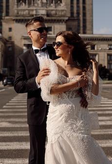 L'uomo e la donna appena sposati in abito da sposa camminano lungo l'attraversamento pedonale sullo sfondo del paesaggio urbano, sorridono felicemente insieme concetto del giorno del matrimonio, si guardano l'un l'altro contro. momenti felici