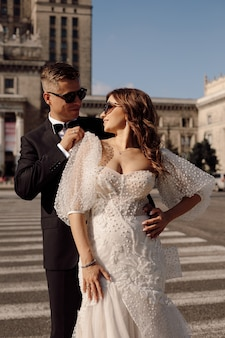 L'uomo e la donna appena sposati in abito da sposa camminano lungo l'attraversamento pedonale sullo sfondo del paesaggio urbano, sorridono felicemente insieme concetto del giorno del matrimonio, si guardano l'un l'altro con gli occhiali.