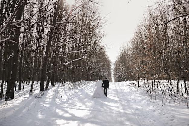 Una coppia di sposi novelli cammina in inverno lungo una strada innevata