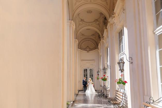 Gli sposi si tengono per mano e camminano su un bellissimo passaggio