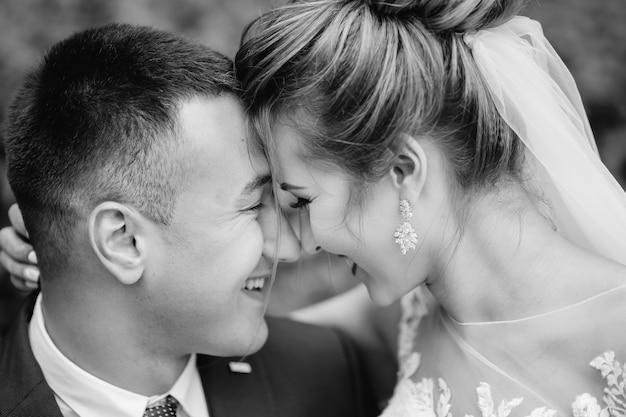 Gli sposi nella fotografia in bianco e nero hanno chiuso gli occhi e hanno chinato la testa. avvicinamento.