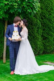 Gli sposi e le damigelle si divertono e mangiano insieme la torta nuziale all'aria aperta durante il banchetto nuziale.
