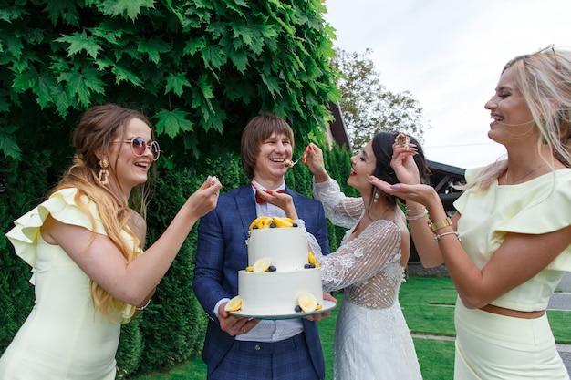 Gli sposini e le damigelle si divertono e mangiano la torta nuziale insieme all'aria fresca durante il banchetto di nozze.