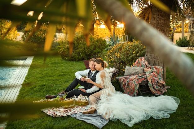 Cena di sposini sul prato al tramonto. una coppia si siede e beve il tè al tramonto in francia.