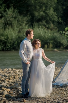 Gli sposi vestiti in stile vintage delle rocce delle montagne sul bellissimo paesaggio