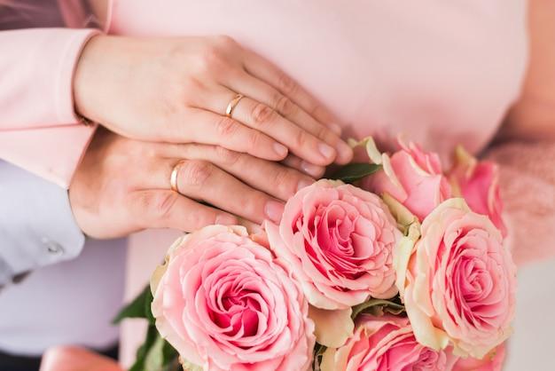 Mani degli sposi con anelli. bouquet da sposa sullo sfondo delle mani della sposa e dello sposo con un anello d'oro