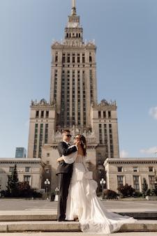 Sposi novelli, uomo e donna in abito da sposa sullo sfondo di un grande edificio alto in città e attraversamento pedonale, si abbracciano, felicemente insieme in occhiali da sole, foto a figura intera.