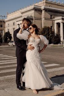 Sposi novelli, uomo e donna in abito da sposa camminano lungo l'attraversamento pedonale sullo sfondo del paesaggio urbano, abbracciando, felici insieme, concetto del giorno del matrimonio. momenti felici