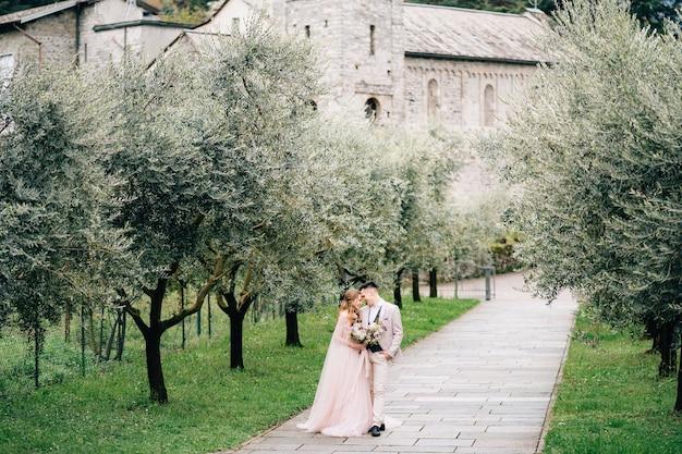 Gli sposi stanno su un sentiero in un uliveto fiorito contro un vecchio edificio