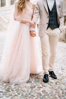 Gli sposi stanno sulle pietre per lastricati contro un vecchio edificio a bergamo italia