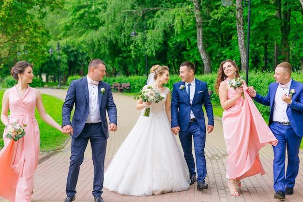 Gli sposi ei loro amici si tengono per mano e camminano nel parco.