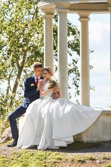 Gli sposi camminano nella natura nel parco dopo la cerimonia nuziale. un bacio e un abbraccio da un uomo e una donna. lo sposo tiene in braccio la sua sposa