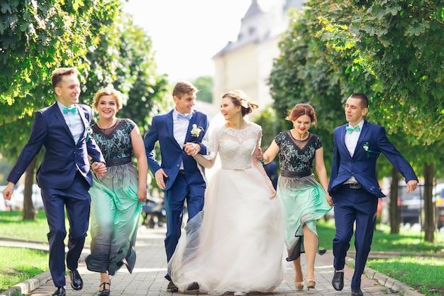 Sposini con damigelle e testimoni che si tengono per mano e si divertono nel parco