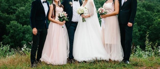 Sposi novelli con testimoni dello sposo e damigelle che si divertono all'aperto. la sposa e le ragazze con mazzi di fiori e lo sposo con gli amici dei ragazzi sono in piedi insieme nella natura.