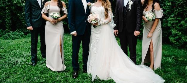 Sposi con testimoni dello sposo e damigelle che si divertono all'aria aperta