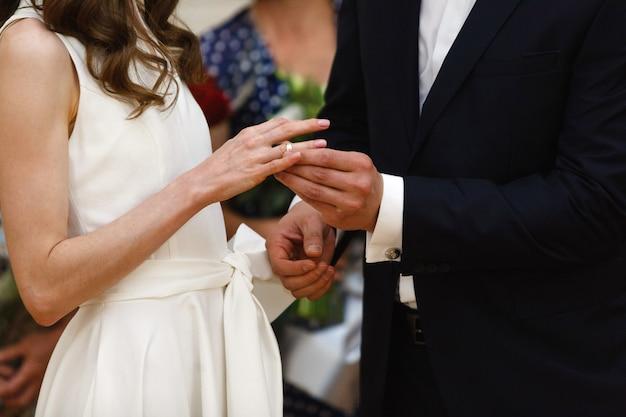 Sposi con anelli sulle dita al giorno delle nozze. cerimonia di matrimonio da vicino. la coppia si scambia gli anelli di nozze d'oro. coppia appena sposata. ha messo l'anello nuziale per lei. lo sposo ha messo l'anello per la sposa