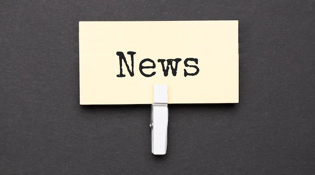 Testo di notizie su carta con clip wihte. su sfondo nero
