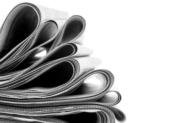 Giornali piegati e impilati su bianco