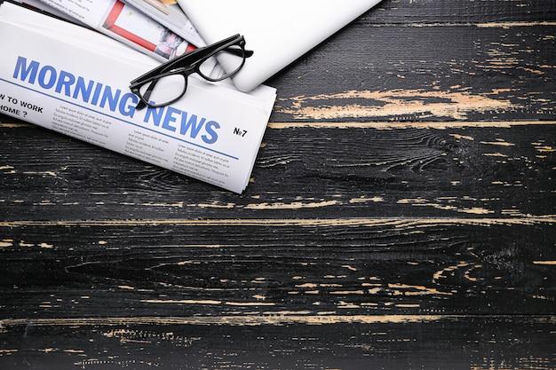 Giornali e laptop su legno scuro