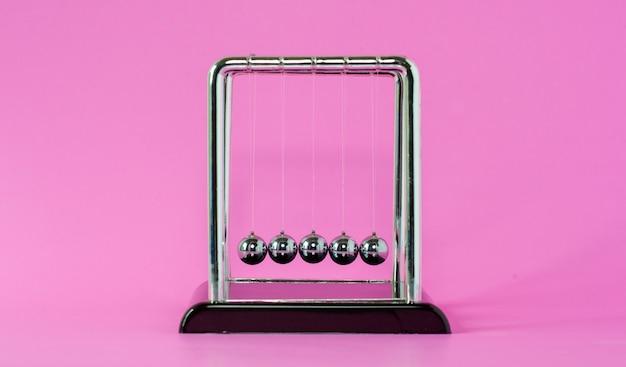 Concetti di fisica della culla di newton per azione e reazione o causa ed effetto sullo sfondo rosa
