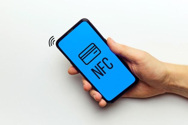 Concetto di pagamento tecnologia wireless nfs con smartphone in mano di persona.