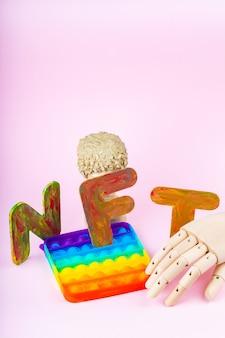 Token non fungibile nft. concetto per il sistema blockchain. statua classica e giocattolo pop it su sfondo rosa. concetto di arte cripto con una mano artificiale