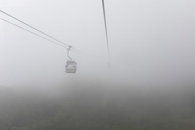 Cabina di funivia di rumore metallico 360 di ngong sulla vista verde del paesaggio della montagna nella stagione delle piogge hong kong