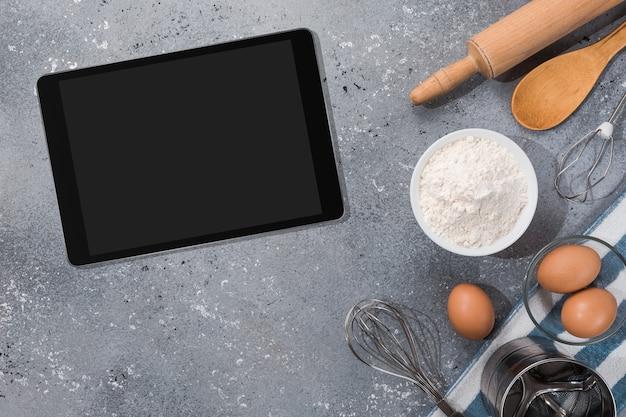 Ngredients, strumenti per la cottura e tablet con schermo vuoto e posto per testo o immagine sul tavolo grigio. ricetta, libro di cucina, modello di corsi di cucina online