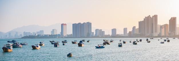 Panorama della città di nha trang, famosa destinazione turistica in vietnam per espatriati russi. baia di nha trang con le barche che galleggiano sull'oceano. hotel dei grattacieli di tramonto sulla spiaggia.