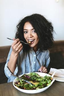 Bella ragazza afro-americana che mangia insalata nel ristorante. ritratto di signora sorridente con capelli ricci scuri e insalata sul tavolo al caffè