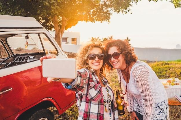 Una bella coppia attraente di donna di mezza età viaggia insieme a un vecchio furgone rosso vintage e si fa selfie con un telefono moderno durante l'attività di svago all'aperto per picnic