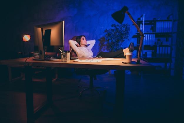 Bello attraente elegante elegante solitario single lady top executive manager marketer avvocato avvocato agenzia proprietario gambe appoggiate sul desktop di notte scuro stile industriale interno posto di lavoro