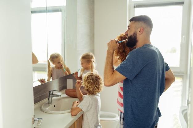 Bel uomo barbuto che mette uno spazzolino da denti in bocca
