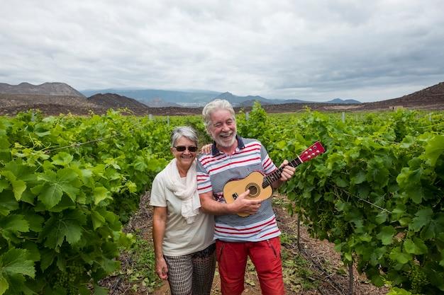 Bella bella coppia adulta capelli bianchi cammina sui campi di vino suonando una chitarra ukulele
