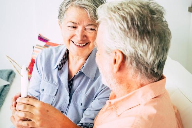 Bella bella donna anziana caucasica allegra che sorride all'uomo seduto con lei