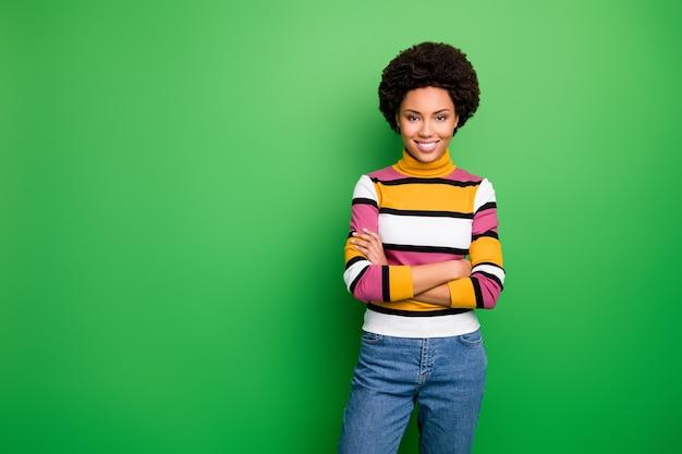 Di bella bella pelle scura donna d'affari ondulata dentata raggiante sorridente buon umore braccia incrociate indossare jeans jumper a righe casual