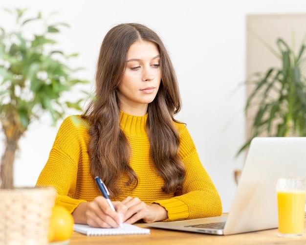 Bella bella femmina con capelli lunghi biondi che lavora al computer portatile seduto a casa.